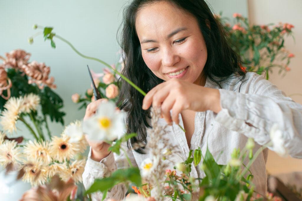 Floral designer maakt boeket en glimlacht vrolijk.